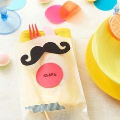Beklebt mit Schnurrbart, Brille und Masking Tape werden aus einfachen Butterbrottüten tolle Bestecktaschen für die Party. Hier finden Sie die Bastelvorlage!