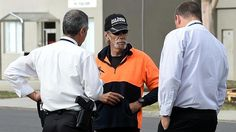 Police speak to a man during a raid on the Rebels bikie clubhouse in Dandenong South this