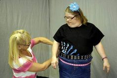"""""""Designs wins award for clothing"""" - The News-Herald, 7/21/13 Karen Bowersox, owner of Downs Designs in Mentor, measures Kelleen Kinnaird for new denim shorts and capris. Bowersox just won $50,000 in a Staples contest to promote her business which designs clothing for people with Down syndrome.  www.downsdesigns.com"""