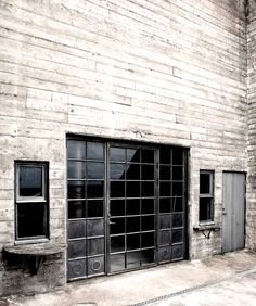 Industrial metal windows and door set into a vast concrete wall | warehouse…