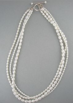 Three Strands of White Rice Shaped Pearls Join for this Necklace. via Etsy.