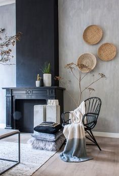The black mantelpiece has become even more eye-catching by painting the wall above it black as well. The rattan armchair is Klaas' favorite item. It belonged to his grandma and by painting this fifties chair black it looks very contemporary. Black Rattan Chair, Rattan Armchair, Rattan Furniture, Upholstered Chairs, Living Room Designs, Living Room Decor, Living Rooms, Interior Walls, Interior Design