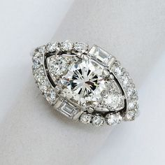A Diamond and Platinum Ring, circa 1955  Set with a round diamond weighing approximately 1.65 carats, within a navette-shaped frame, further decorated with smaller round and baguette-cut diamonds, mounted in platinum