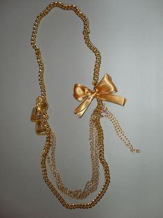 Collar largo dorado con detalles de corazones y moño dorados