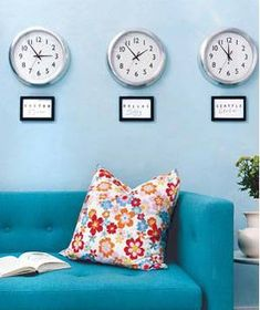 Three clocks hanging above a sofa