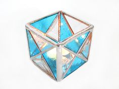 This is a stained glass candle holder made of blue stained glass and gluechip bevels. Each side is a square made of four trinagles, the bottom is made of mirror. The candle holder is approximately 3 x 3 x 3 inches. It sparkles and casts wonderful shadows all around. Looks great lit or not!    The candle holder was made using the copper foil or Tiffany style method - so no lead came was used. The seams are shiny silver color. I photographed this candle holder in different lighting to better…