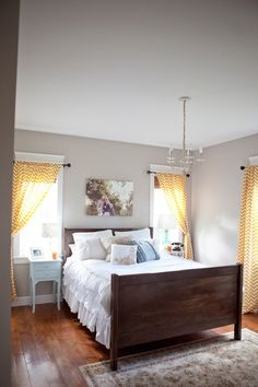 I love this clean simple master bedroom-the dark wood of the bed and the curtains are wonderful to me! Great way to work with a small space