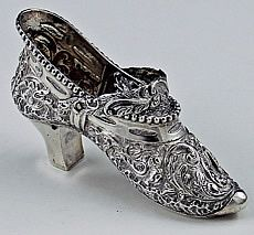 "Dutch Silver Miniature Shoe    A Dutch hallmarked silver shoe with chased decoration on the sides and on the bottom of the shoe. Length: 3 3/4"". Weight: 1.7 troy oz. Ht: 2 1/4""A small hand chased handle swivels to extend upwards."