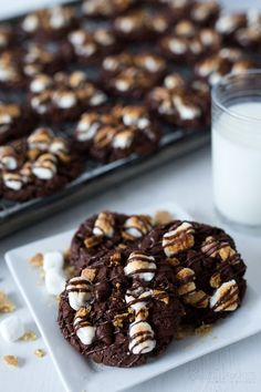 Chocolate S'mores Cookies with a fudgy, chocolate cookie base studded with chocolate chips, topped with graham crackers and marshmallows, toasted and finished with a drizzled of chocolate.