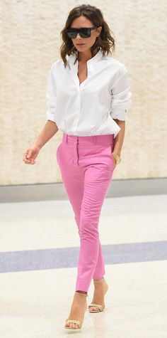 Victoria Beckham arrived at JFK looking NYFW-ready in a crisp white shirt tucked into a cheery pair of bubblegum-pink slim-leg trousers, complete with her usual VB shades and neutral sandals.