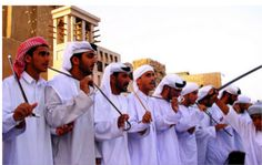 Arts:This is UAE men performing a cultural dance called the Ayyalah. It is the most beloved folk dance in the whole country. Men link elbows, and go in 2 lines and use camel sticks which pose as swords, and get led by the drum called the Al-Ras. There is usually between 25 and 200 men performing in this, and they react a battle scene. It is mostly performed around the Burj Khalifa hotel.