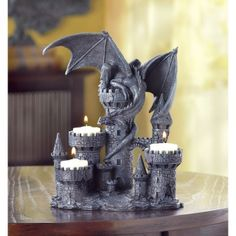 """by Dragon Crest In a scene from countless tales, a medieval castle is besieged by a fierce winged predator. Perched upon the highest tower, he presides over the three flickering candle flames that top the other ramparts. A legendary decoration even when unlit! 7.5"""" x 5.12"""" x 9.25""""  www.allgooddecor.com/shop.html #allgooddecor #decorations #gifts #candles #toys #discount #furniture #candleholders #home #figurines #lighting #pictures #mirrors #jewelry #garden #clearance #kitchen #bedandbath"""