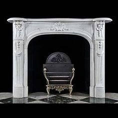 A compact Louis XV fireplace mantel carved in white statuary marble, the serpentine shelf over a panelled frieze centered by a small palmette scrolled cartouche flanked by scrolled top jambs which descend into panelled supports. French late 19th early 20th century.