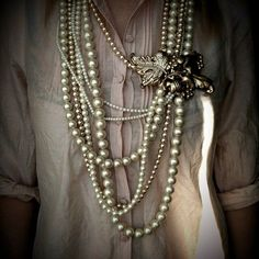 Gather a bunch of multi-length pearl necklaces and clasp them together with a vintage brooch!
