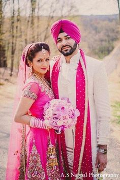 An Indian bride and groom pose for pictures after their Sikh wedding ceremony.