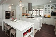Stunning kitchen with white cabinets paired with black marble countertops and mini subway tile backsplash.