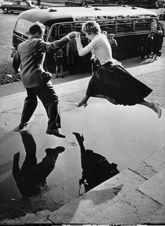 A man gives a woman a helping hand as she takes a flying leap over a large puddle on the pavement (1960).