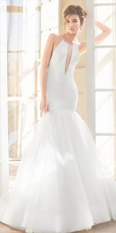 Ivory crepe fit to flare bridal gown, halter neckline with plunging keyhole detail, complete illusion low back, full tulle skirt with sparkle underlay, horsehair hem detail and chapel train.