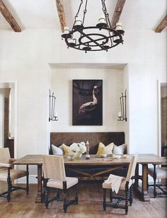Tufted seating nook, exposed wood beams, chandelier, dining table, sconces.