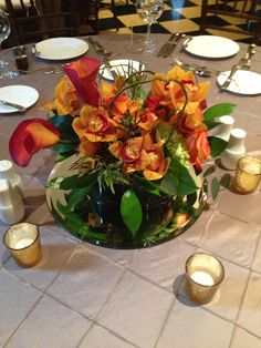 Orange, red and green flowers including hydrangea, roses and orchids,