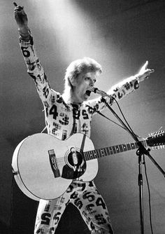 David Bowie performing in England during the Ziggy Stardust tour on January 7, 1973 in red jumpsuit with black and white tartan numbering.