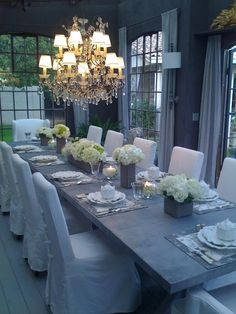 Crystal chandelier, zinc table, gray walls with the contast of the light drapery and slipcovers.  Love it!