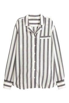 Chemise à larges rayures: Chemise en tissu aérien à larges rayures. Modèle avec col et revers. Fausse poche en haut et boutonnage devant. Poignet boutonné souligné par passepoil contrastant. Base arrondie.