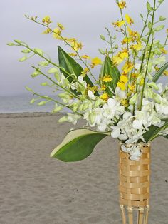 ceremony decor, tiki torch used to hold aisle flowers for this beach wedding