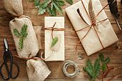 Group of homemade wrapped holiday presents with nature elements on wood surface