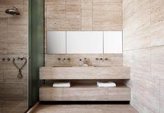 I bagni rivestiti in travertino chiaro di una casa a Roma progettata da Fanny Bauer Grung e David Lopez Quincoces