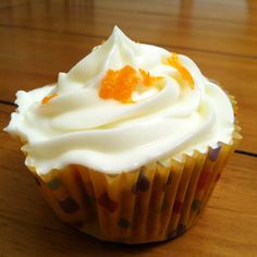 Carrot cake cupcake topped with cream cheese icing & shaved carrots.