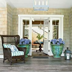 This wide front porch boasts a welcoming entryway. Wicker furniture and Hamptons-style shingles give the front door classic style. Coastalliving.com