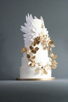 Olympia | Wedding Cake design By Victoria Watkin | A stunning and original wedding cake inspired by nature and Greek legend. This cake is a big statement for those wanting something spectacular but still beautiful and elegant. Graceful sugar wings arc above a wreath of gold leaf covered sugar leaves, and is sure to be a memorable addition to your reception. White blossoms could also be added to the wreath to addd a more feminine aspect.