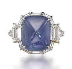 A SAPPHIRE AND DIAMOND RING   Set with a sugarloaf cabochon sapphire, weighing approximately 18.19 carats, to the tapered baguette-cut diamond surround and shoulders, mounted in platinum