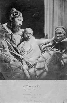 The sick Captain Speedy triumphantly poses with the dead Emperor Tewodros II's child heir and a defeated Ethiopian guard.