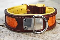This particular collar is a 2 inch wide brown leather with copper alligator print inlay.  Tapering down to 1.5 inches at the strap to buckle.  1.5 inch center d-ring with stainless steel backplate for lead walking.  Yellow patent leather padded lining making it soft and comfortable on the dog's neck.