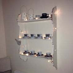 Coffee cups & fairy lights brighten up dark shelves.