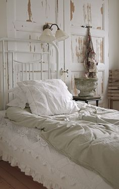 three extra tall doors in shabby chic white create a paneled wall behind a white iron bed......sweet dreams.....