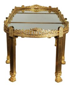 A Very Fine and Large French Empire Style Napoleon III Gilt-Bronze Surtout-de-Table, now a coffee table with later gilt-bronze legs with paw-feet, with a finely chased grape and vine border and mirror plate top, in the manner of Pierre-Philippe Thomire (French, 1751–1843). The gilt-bronze legs are Circa: Paris, 1900. The Surtout-de-Table is Circa: Paris, 1860-1870