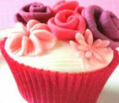 Cupcakes in pirottini rossi ricoperti da pasta di zucchero bianca con fiori e rose colorate