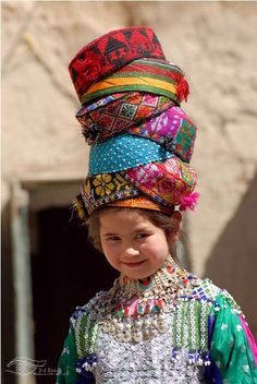 "This reminds me of the children's  story ""Caps for Sale"". Afghan girl selling hats."