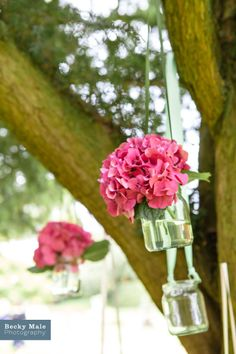 Hydrangeas in jars hanging from trees, an excellent way to add a dash of colour to an outdoor wedding area. www.beckymalephotography.com
