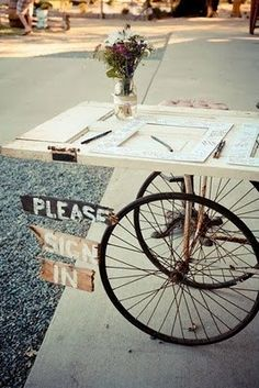 Old door on bicycle wheels ... Signage clipped to the wheel.