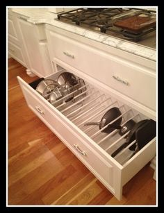 "Looking for a better way to store your pots, pans, and casserole dishes? If you have a deep drawer, set up a vertical ""filing"" system with the help of a few dividers. Each dish and lid gets its own space, and you don't have to worry about messy, piled-up dishes taking over your cupboards."
