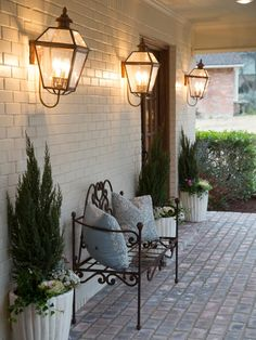 Show hosts Chip and Joanna Gaines knew that a front porch would really make this house a home. By extending the roofline, they were able to create this breezeway porch with vintage light sconces and an ornate wrought-iron bench.