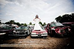 Im thinking we can have her staanding on top of some beat up cars, dressed up, not in a wedding gown tho