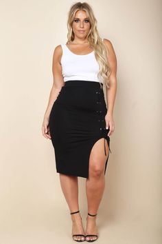 A plus size midi peg skirt with a leg slit and lace up details. Features an elasticized waistline. Solid colored all over.