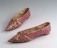 A pair of pink glace kid slippers with stylized pattern of black floral moverall (stenciled!); pointed toe; very low heel covered with pink leather; pink silk cord ties single pair of eyelet holes at front; narrow ribbon covers seam