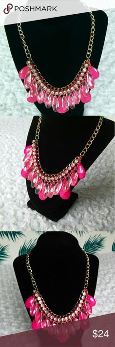"Boutique Hot Pink and Crystal Statement Necklace Faceted acrylic faceted clear and hot pink teardrop of varying sizes dangle from a hot pink satin ribbon woven through a  gold tone chain with clear sparkling crystals across the top border. This is used but has very little wear. The chain is rough on the right side. The chain is 18"" with a 2"" drop on the largest teardrops. Jewelry Necklaces"