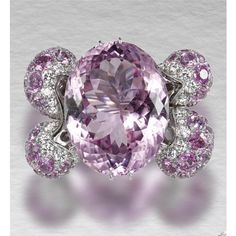 KUNZITE, PINK SAPPHIRE AND DIAMOND RING Centring on an oval faceted kunzite, the shoulders of bombé design pavé-set with circular-cut pink sapphires and brilliant-cut diamonds.